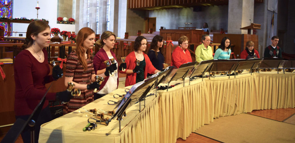 the bell choir arrayed behind a table holding bells at the front of the sanctuary