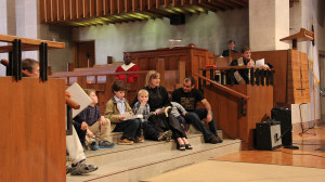 children gathered at the front of the sanctuary, sitting on steps