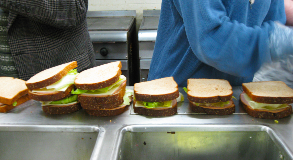 sandwiches lined up on a counter, being made by the grad study participants