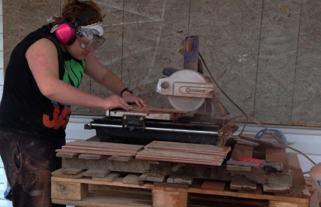a young person using a power saw to cut wood
