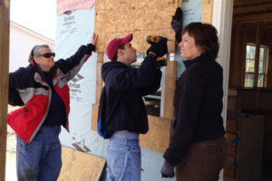three people standing in front of a house being built on a mission trip