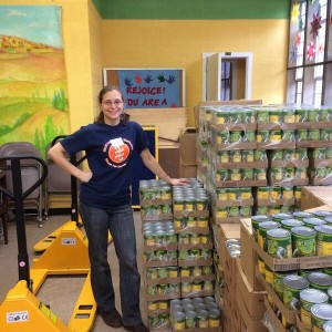 volunteer stands in front of pallets of canned goods during pantry setup