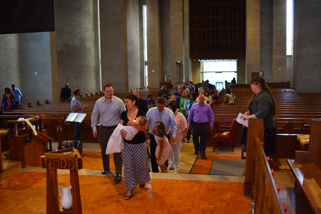 crowd of churchgoers streaming down the aisle to the front of the sanctuary