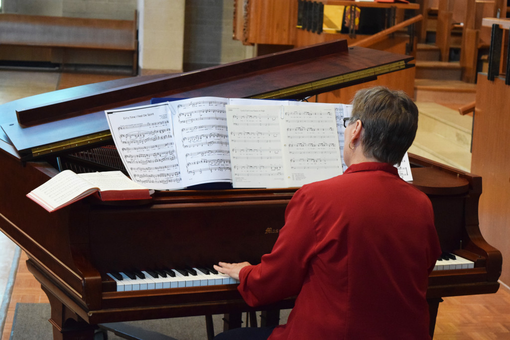 a person plays a piano at the front of the sanctuary