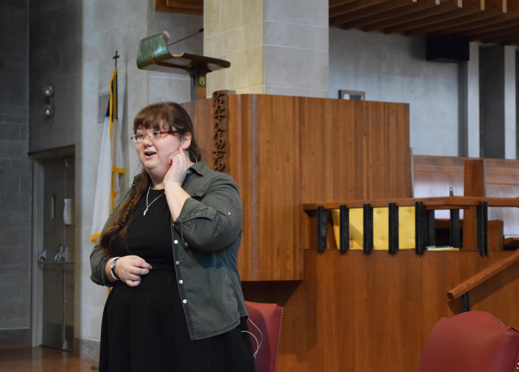 woman stands at front of sanctuary speaking into a head-mounted microphone