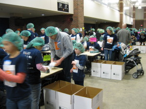 a large group of people in a big hall, wearing hairnets as they package food