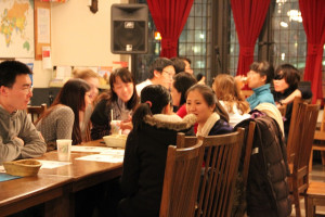 a diverse group gathers around a table in etc. coffeehouse