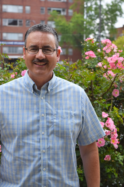 Pastor Dan King Crede posing in front of a flower bush in Wesley's parking lot