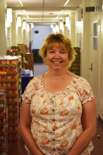 Vicki standing in the hallway outside the conference room with cans of food for the Wesley Evening Food Pantry set up behind her