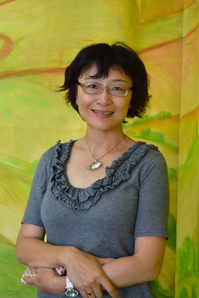 Jie Wu Smith standing in front of a painted backdrop in Wesley's nursery